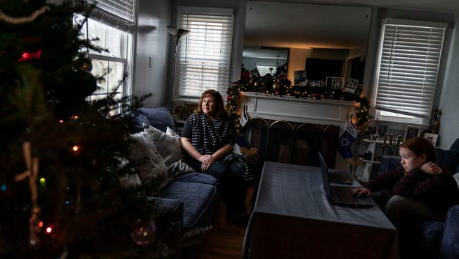 Eileen Carroll, left, sits for a portrait as her daughter, Lily, 11, attends school remotely from their home in Warwick, R.I, Wednesday, Dec. 16, 2020. When Carroll's other daughter tested positive for the coronavirus, state health officials told her to notify anyone her daughter might have been around. Contact tracers, she was told, were simply too overwhelmed to do it. It's the same story across the U.S., as a catastrophic surge in infections has made it difficult or impossible to keep up with the calls considered critical to controlling outbreaks.