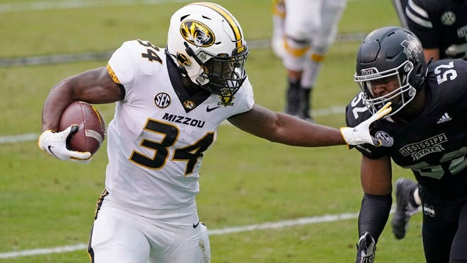Missouri running back Larry Rountree III (34) fights off an attempted tackle by Mississippi State defensive end Kobe Jones (52) on his way to a 18-yard touchdown run during the first half of an NCAA college football game, Saturday, Dec. 19, 2019, in Starkville, Miss.