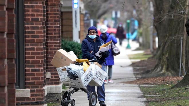 """FILE - A U.S. postal worker delivers packages, boxes and letters Tuesday, Dec. 22, 2020, along her route in the Hyde Park neighborhood of Chicago, just three days before Christmas. Some Christmas gift-givers discovered their presents didn't arrive in time for the holiday despite ordering weeks ahead. The U.S. Postal Service says it faces """"unprecedented volume increases and limited employee availability due to the impacts of COVID-19."""""""