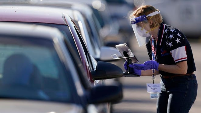 FILE - In this Tuesday, Nov. 3, 2020 file photo, an election worker instructs a voter at a drive-through polling location in Kansas City, Mo. The location was established to provide access for people who have tested positive for COVID-19 and elderly voters.