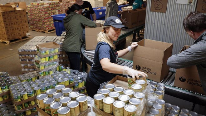 Staff and volunteers unpack crates of nonperishable food at the Mid-Ohio Food Collective.