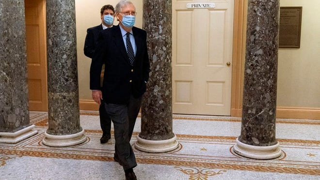 Followed by a staffer, Senate Majority Leader Mitch McConnell of Ky., right, leaves the Capitol for the day, Tuesday, Dec. 29, 2020, on Capitol Hill in Washington.