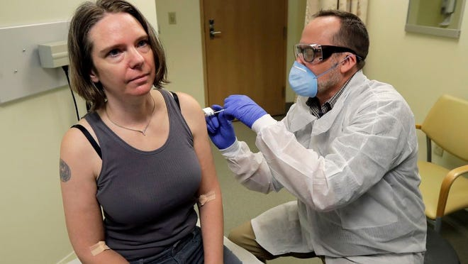 FILE - In this March 16, 2020 file photo, a pharmacist gives Jennifer Haller, left, the first shot in the first-stage safety study clinical trial of a potential vaccine for COVID-19, the disease caused by the new coronavirus, at the Kaiser Permanente Washington Health Research Institute in Seattle. Tens of thousands of Americans have volunteered to test COVID-19 vaccines, but only about half of them got the real thing. Now, with the first vaccine rollouts and a surge in coronavirus infections, experts are debating what to do about the half that got a dummy shot.