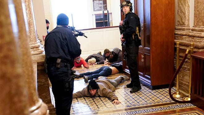 U.S. Capitol Police hold protesters at gun-point near the House Chamber inside the U.S. Capitol on Wednesday, Jan. 6, 2021, in Washington.