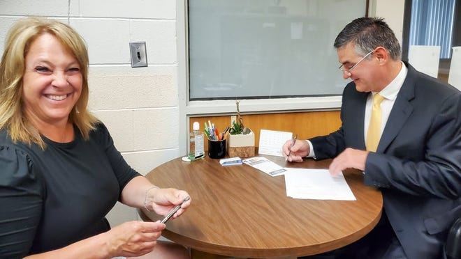 New Mason Consolidated Schools Supt. Kelli Tuller smiles as the district's Board of Education President Bruce Stieben signs her contract.
