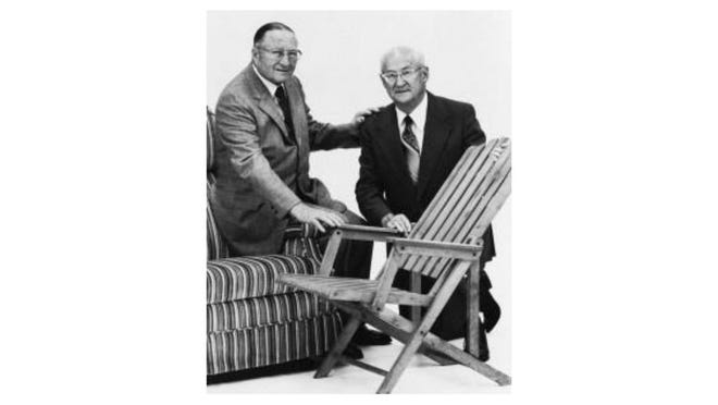 La-Z-Boy founders Edward Knabusch and Edwin Shoemaker pose for a photo by what was their first reclining chair and the product of their 1931 patent.
