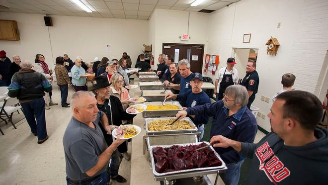 Members of the Monroe Fire Department and volunteers, seen serving the annual Pre-Thanksgiving Turkey Dinner in 2014.