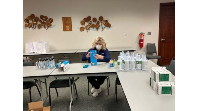 Molly Luempert-Coy of the DTE Energy community relations staff works on packing Back to Work Tool Kits for local small businesses.