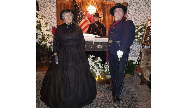 Lila Fedokovitz, chairman of the Flat Rock Historical Commission and a member of the Flat Rock Historical Society, dresses in black and joins Bob Coch, a local military historian and former re-enactor, for a past portrayal of President Lincoln's funeral at the historic Langs-Wagar House located behind the Flat Rock Library. Coch dressed up as one of Lincoln's Honor Guards from the Michigan 24th Iron Brigade during the wake held at a previous Cemetery Walk.