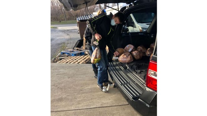 Camden Schmidt, a member of the Monroe County 4-H Club, Teen Ambassadors, loads hams to be donated to local families.