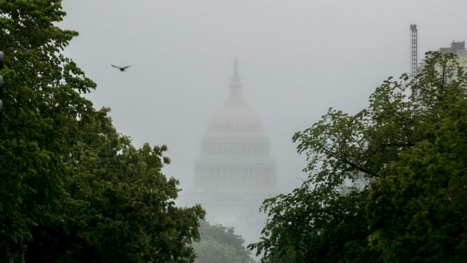 FILE - In this May 22, 2020, file photo the Dome of the U.S. Capitol Building is visible through heavy fog in Washington.