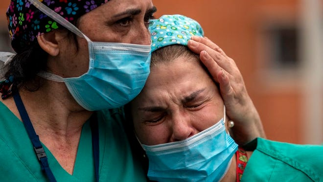 Health workers cry during a memorial for their co-worker who died from COVID-19, on April 10, 2020. AP Photo/Manu Fernandez
