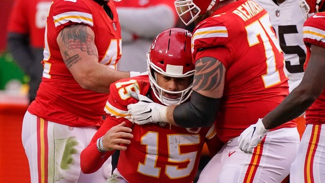 Kansas City Chiefs quarterback Patrick Mahomes (15) is helped off the field by teammate Mike Remmers, right, after getting injured during the second half of an NFL divisional round football game against the Cleveland Browns, Sunday, Jan. 17, 2021, in Kansas City.