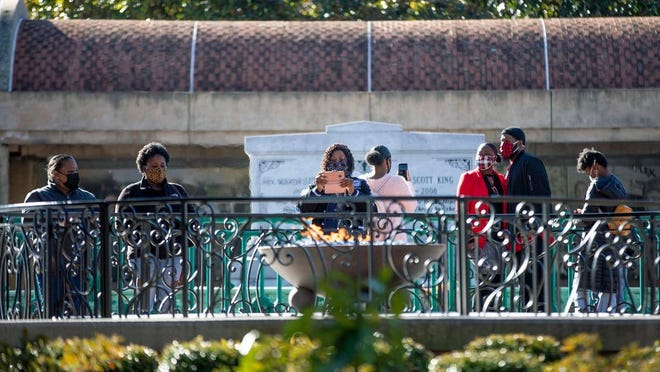 People visit the eternal flame at the tomb of Rev. Martin Luther King Jr. and his wife Coretta Scott King on Monday, Jan. 18, 2021, to celebrate the Martin Luther King Jr. holiday, in Atlanta.