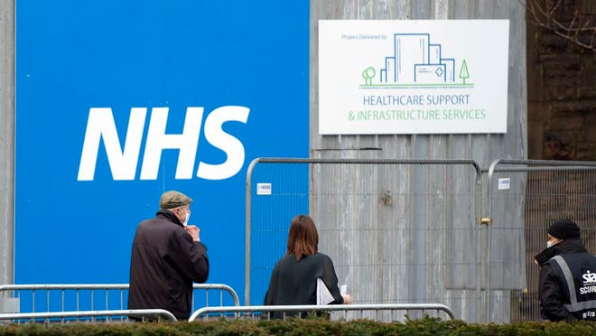 A member of the public arrives at Blackburn Cathedral, which is being used as a mass vaccination center during the coronavirus outbreak in Blackburn, England, Monday Jan. 18, 2021. The first 24-hour vaccination centers will be piloted in London before the end of January, the UK's vaccines minister Nadhim Zahawi has said.
