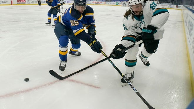 San Jose Sharks' Erik Karlsson (65) passes around St. Louis Blues' Jordan Kyrou (25) during the first period of an NHL hockey game Monday, Jan. 18, 2021, in St. Louis.