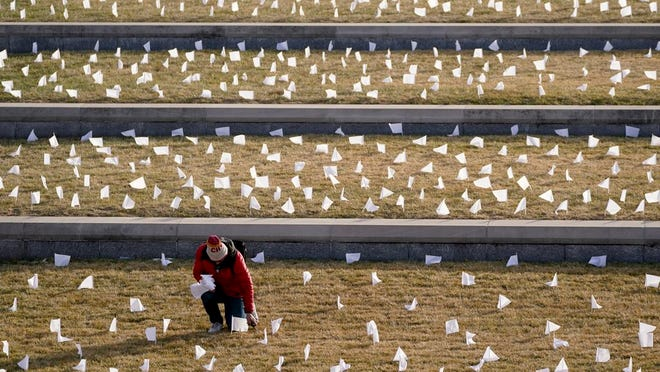 A man places flags at the National World War I Museum and Memorial Tuesday, Jan. 19, 2021, in Kansas City, Mo. The 1,665 flags represent the area residents who died in the coronavirus pandemic and the display was part of a national memorial to lives lost to COVID-19.