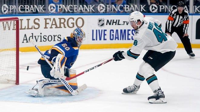 San Jose Sharks' Tomas Hertl, right, scores the game winning goal past St. Louis Blues goaltender Jordan Binnington during a shootout of an NHL hockey game Wednesday, Jan. 20, 2021, in St. Louis.