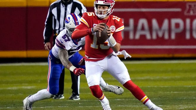 Kansas City Chiefs quarterback Patrick Mahomes (15) scrambles up field ahead of Buffalo Bills defensive end AJ Epenesa (57) during the first half of the AFC championship NFL football game, Sunday, Jan. 24, 2021, in Kansas City, Mo.