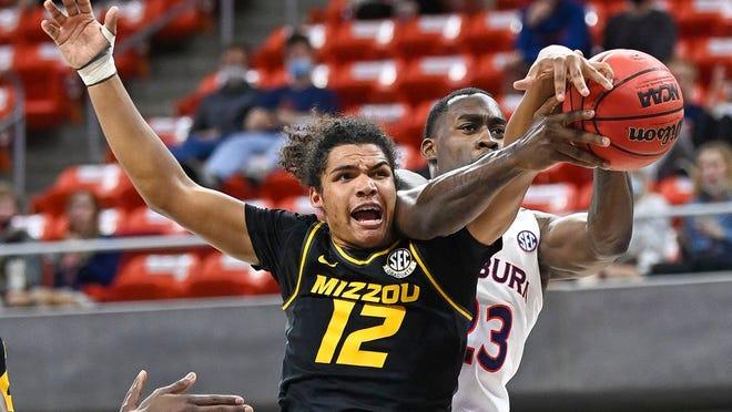 Missouri guard Dru Smith (12) and Auburn forward Jaylin Williams (23) reach for a rebound during the first half of an NCAA college basketball game Tuesday, Jan. 26, 2021, in Auburn, Ala.
