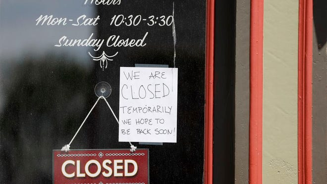 A sign hangs in the window of a popular sandwich shop that has temporarily closed due to the coronavirus Friday, May 1, 2020, in St. Louis.