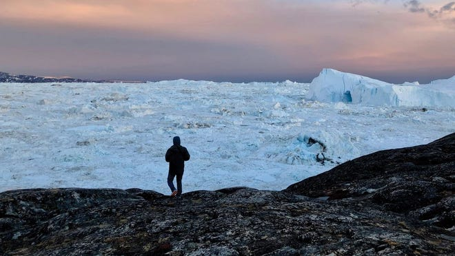 Sanitago de la Peña, a researcher from the Byrd Center, looks out at large icebergs near Ilulissat in western Greenland in May 2019.