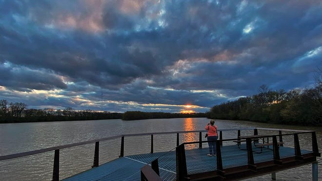 Wendy Hills takes in the sunset at Scioto Audubon Park April 13, 2020. Wendy who works as a nurse at OSU said she had heard on the news that the sunset was going to be good and wanted to take it in.