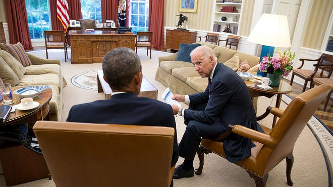 Vice President Joe Biden meets with President Obama in the Oval Office recently. Obama has acknowledged that his policy decisions will be a factor in next month's midterm elections — although Obama's name will not appear on any ballots.