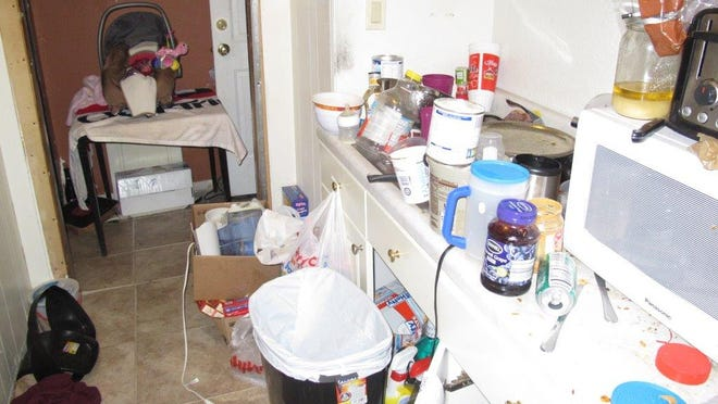 Kitchen counters were lined with debris when officials arrived at home in the 200 block of Second Street Southeast. Officials also found a running, open oven; dirt; and human feces.