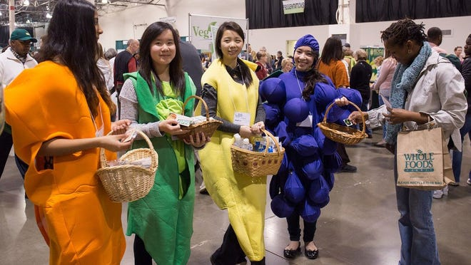 Women dressed as fruits and veggies greet attendees at the 2014 VegFest held at the Suburban Collection Showplace in Novi.