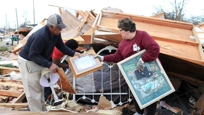 Lee Eddie Varnado, left, and volunteer Sylvia Berry sift through rubble in search for family photos in Columbia Friday. Around 2:30 p.m. Tuesday evening a F3 tornado ripped through Columbia leaving four dead and causing massive damage to buildings and property.