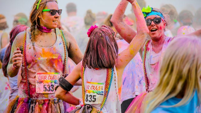 Color Craze runners exchange high-fives and smears of bright paint.