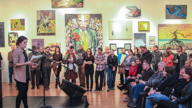 Lauren Smart shares her art review with the audience at Critical Mass 3 opening reception.