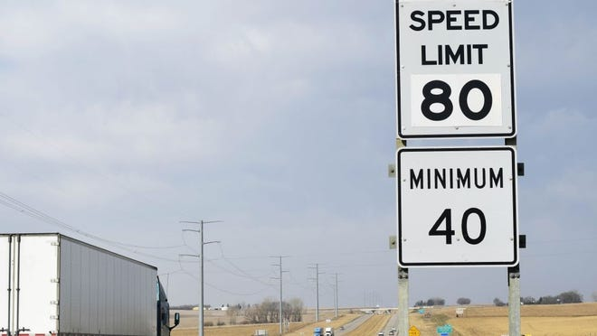 A semi-tractor trailer passes by an 80-mph speed limit sign on Interstate 90 near Brandon.
