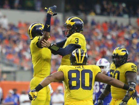 Michigan's Tarik Black, left, celebrates with Wilton