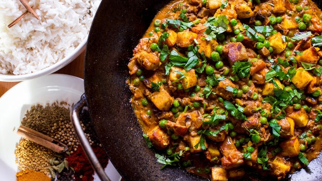 Matar Paneer is about to be served with long grain white rice, spices and curries.