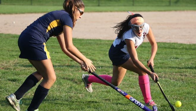 Byram Hills' Autumn Lauria moves the ball in front of Pelham's Alissa Manos during their field hockey game in Armonk, Oct. 8, 2015.