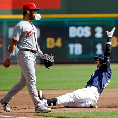 Ryan Braun slides into third base for a triple Sunday as Eugenio Suarez of the Cincinnati Reds blows a bubble during the first inning at Miller Park.