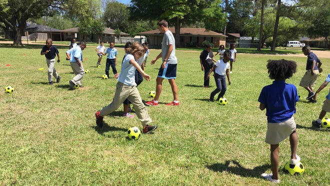 Martin Iddon (center), coordinator of club programs and education with Crossroads Soccer, leads Mabel Brasher Elementary second-graders Thursday in a game that incorporates soccer skills.
