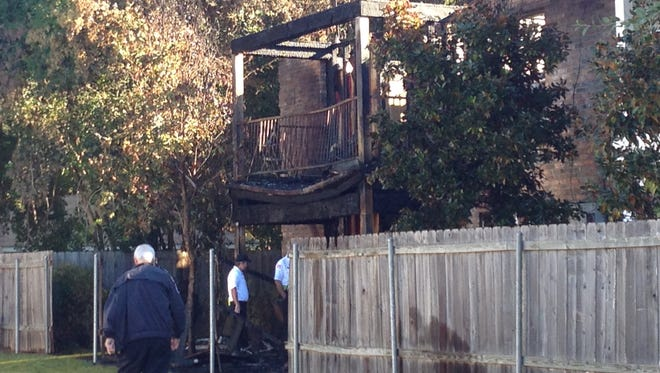 Fire department personnel investigate Monday after an early morning fire heavily damaged some apartments in Alexandria.