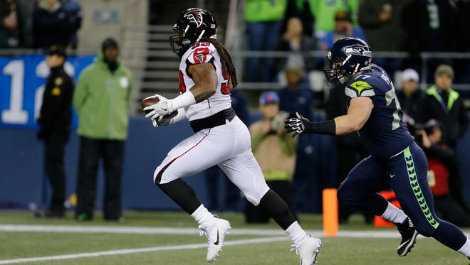 Atlanta Falcons defensive end Adrian Clayborn returns a fumble for a touchdown in the first half of an NFL football game against the Seattle Seahawks, Monday, Nov. 20, 2017, in Seattle.