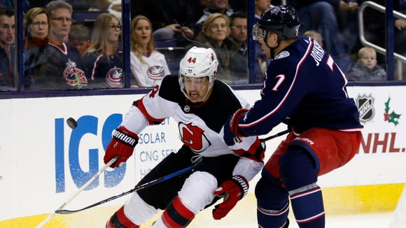 New Jersey Devils forward Miles Wood, left, chases the puck against Columbus Blue Jackets defenseman Jack Johnson during the first period of an NHL hockey game in Columbus, Ohio, Tuesday, Dec. 5, 2017.