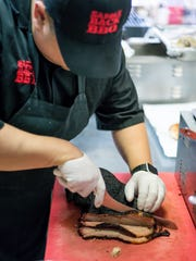 Saddleback Barbecue co-owner Matt Gillett slices brisket.