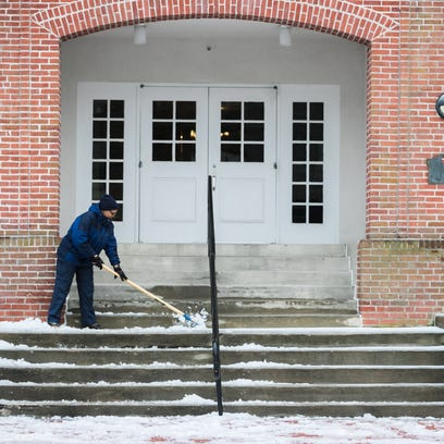 A woman clears frozen ice off the steps of University