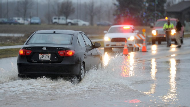 Traffic moves cautiously through high water across Verlin Road in Bellevue December 14, 2015. Constant rain has caused creeks across the area to flood.