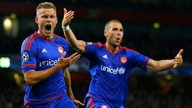 Olympiakos' Alfred Finnbogason, left, celebrates after scoring his side's third goal during the Champions League Group F soccer match against Arsenal.