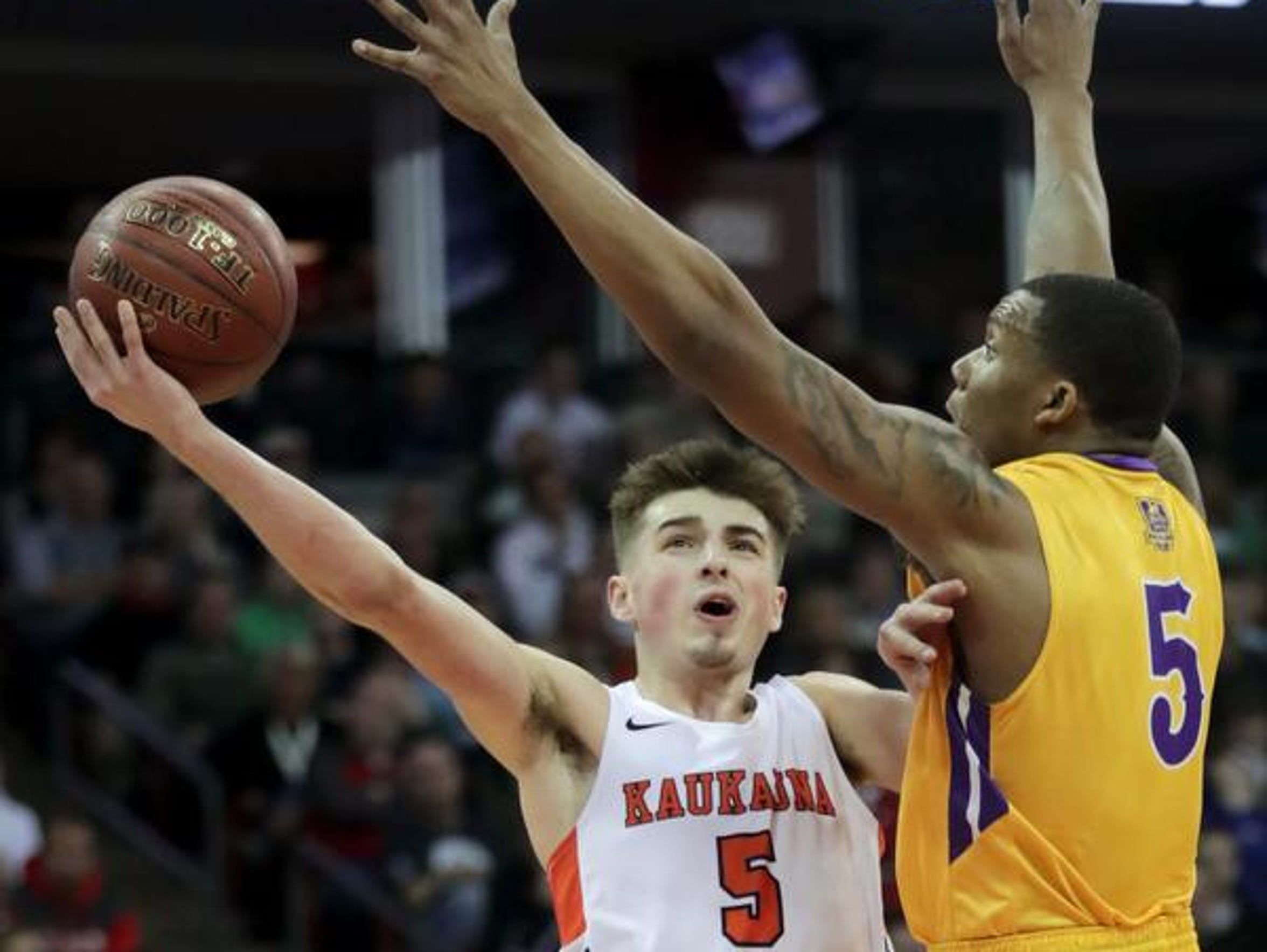 Kaukauna High School's Jordan McCabe goes up for a shot around Milwaukee Washington High School's Deontay Long during their WIAA Division 2 state championship game on Saturday, March 17, 2018, at the Kohl Center in Madison.