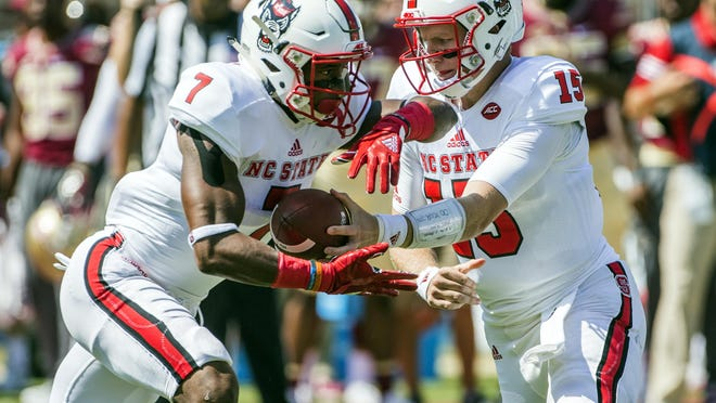 """North Carolina State running back Nyheim Hines, taking the handoff from quarterback Ryan Finley, said the Louisville game has """"been circled on a lot of people's calendars probably in the locker room."""" The Cardinals beat the Wolfpack 54-13 last season."""