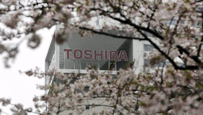 The logo of Toshiba Corp., with cherry blossoms in full bloom at its headquarters in Tokyo, Japan, April 11,  2017.