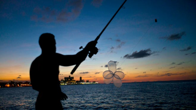 """In this Nov. 13, 2016 photo, mechanic Junior Torres Lopez casts his fishing rod prepared with condoms, known as """"balloon fishing,"""" along the Malecon seawall in Havana, Cuba. When the contraceptives are the size of balloons, fishermen tie them together by their ends, attach them to the end of a baited fishing line and set them floating on the tide until they reach the end of the line, as far out as 900-feet."""